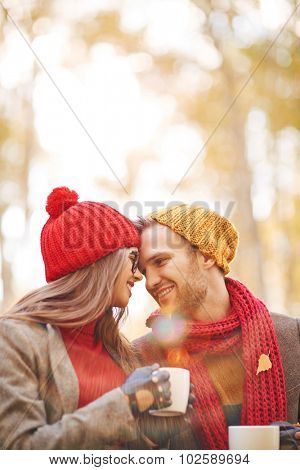 Amorous young couple with tea relaxing outdoors