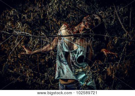 Horrible bloody zombie girl standing outdoor. Halloween.