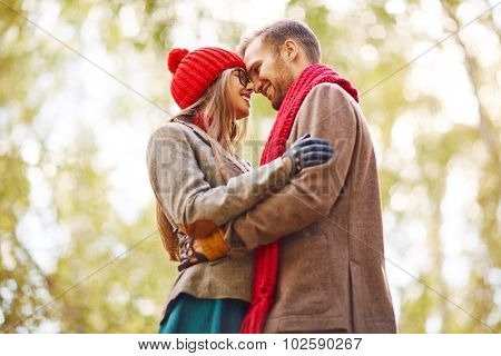 Affectionate couple in stylish casualwear embracing in park