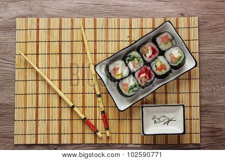 Sushi rolls on a plate on bamboo brown straw mat with chopsticks top view