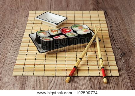Sushi rolls on a plate on bamboo brown straw mat with chopsticks close up