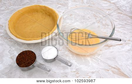 Lined Pie Dish, Beaten Egg And Measuring Cups Of Sugar