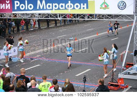 Athletes run to the participants of the marathon finish line