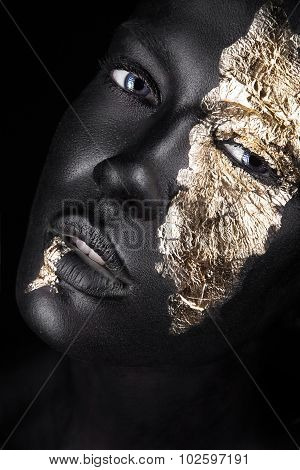 fashion portrait of a dark-skinned girl with gold make-up. Beauty face.