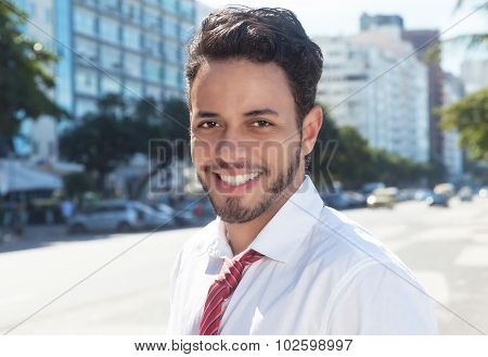 Laughing latin businessman in the city