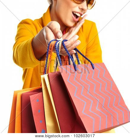 Woman wearing autumn overcoat holding shopping bag.