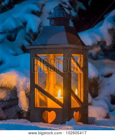 a lantern lights up the snow at christmas. romantic light on one evening in winter. peace and quiet
