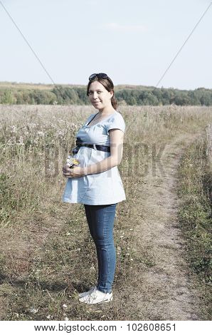 Young pregnant woman in field with a bunch of wild flowers