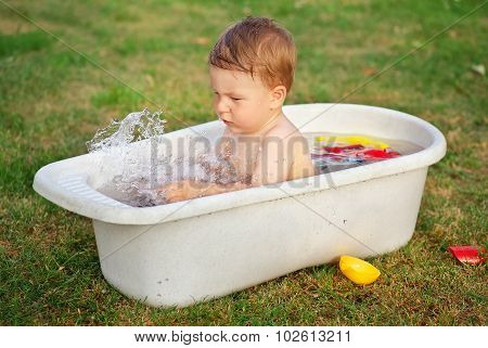 A Small Baby Bathed In The Bath And Playing With Toys.