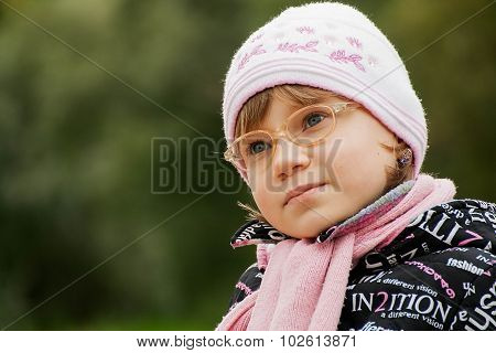 Cute Child Girl In Glasses Sits On A Park Bench