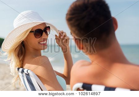love, travel, tourism, summer and people concept - smiling couple on vacation sunbathing on beach