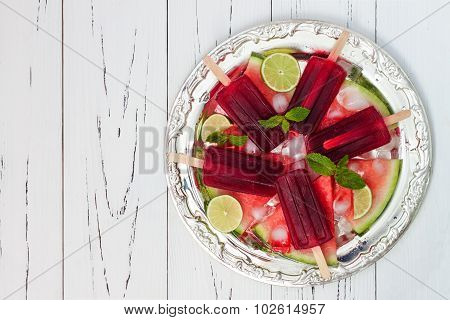 Watermelon mojito popsicles - ice pops - on slices of ripe juicy organic watermelon served on vintag