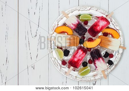 Colorful homemade popsicles with fresh fruits and berries on ice cubes in vintage silver tray