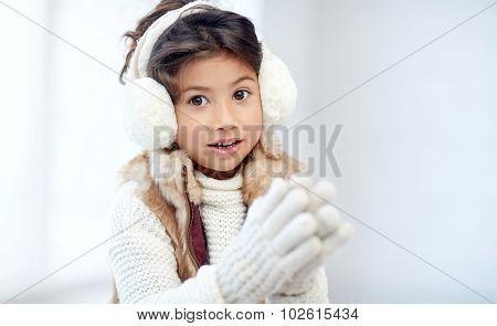 winter, people, happiness concept - happy little girl wearing earmuffs