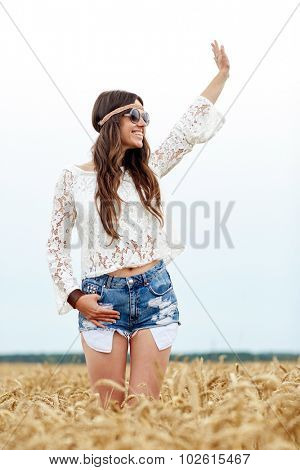 nature, summer, youth culture, gesture and people concept - smiling young hippie woman in sunglasses on cereal field waving hand