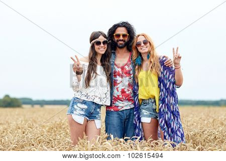nature, summer, youth culture, gesture and people concept - smiling young hippie friends in sunglasses showing peace hand sign on cereal field