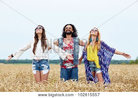 nature, summer, youth culture and people concept - smiling young hippie friends on cereal field enjoying freedom