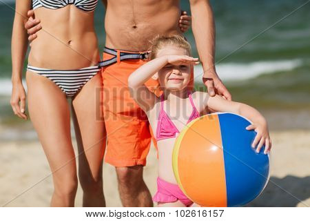 family, childhood, travel and people concept - close up of happy man, woman and little girl in sunglasses with inflatable ball on summer beach