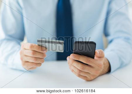 business, technology, cash free and internet people concept - close up of male hands holding smart phone and credit card at office