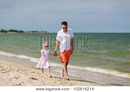 family, travel, vacation, adoption and people concept - happy father with little girl in sunglasses walking on summer beach