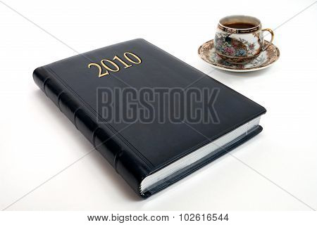 diary and cup of coffee
