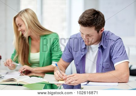 education, people, friendship, technology and learning concept - group of happy high school students or classmates with with textbooks and tablet pc computer learning in classroom