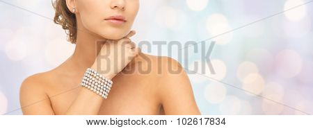 beauty, luxury, people, holidays and jewelry concept - close up of beautiful woman with pearl earrings and bracelet over blue lights background