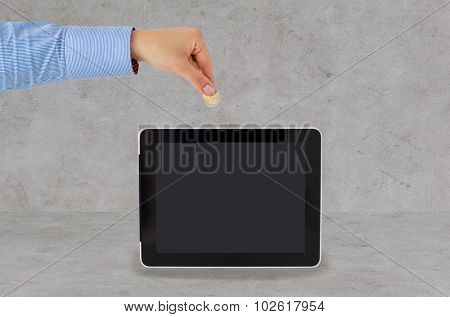 business, finance, investment, money saving and e-commerce concept - close up of hand putting coin into into tablet pc computer with black blank screen over gray concrete background