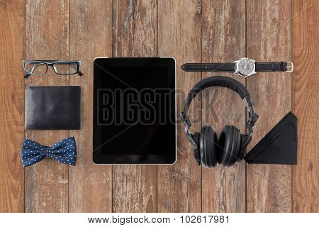 hipster personal stuff and objects concept - tablet pc computer, headphones, wallet, eyeglasses and wristwatch on wooden table background