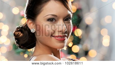 people, holidays, jewelry and luxury concept - smiling woman face with diamond earring over christmas lights background