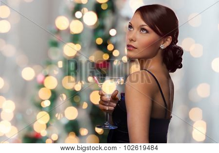 party, drinks, holidays, luxury and celebration concept - woman in evening dress with cocktail over christmas tree lights