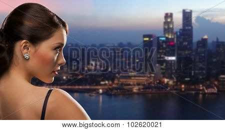 people, holidays, jewelry and luxury concept - woman face with diamond earring over night singapore city background