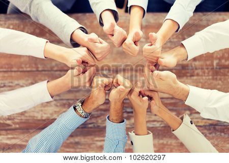 business, people, gesture and team work concept - close up of creative team showing thumbs up and sitting at table in office
