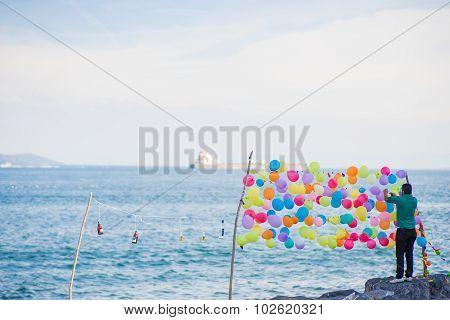 Man In Green Tying Colorful Balloons For Shooting