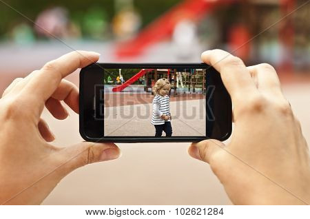 Woman Taking A Photo Of Baby Girl With Smartphone