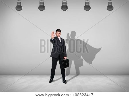 Businessman stands with shadow on the wall