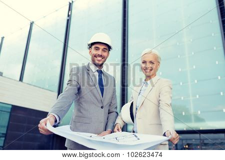 business, partnership, architecture and people concept - smiling businessman and businesswoman with blueprint and helmets on city street