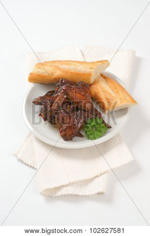 plate of roasted wings and fresh baguette on white place mat