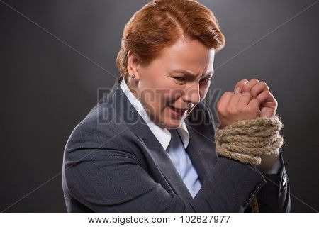 Businesswoman's hands tied up with rope