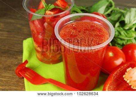 Vegetable and fruit  salad and healthy fresh drink in plastic cups on wooden background. Colorful diet concept