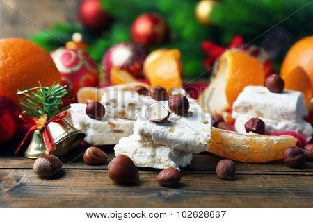 Sweet nougat with oranges and Christmas decoration  on table close up