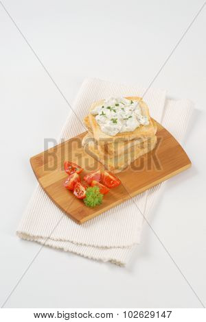 stack of fresh toasts with chives spread on wooden cutting board and white place mat