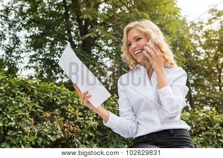 Freelance lady speaking over mobile phone oudoors