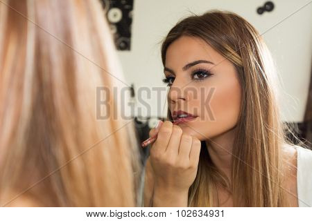 Teenage girl applying makeup on lips