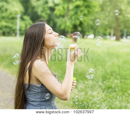 Young Woman Blowing Bubbles