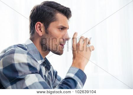 Side view portrait of a handsome man drinking water isolated on a white background