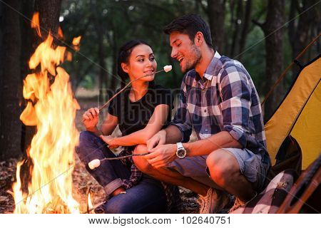 Happy couple fried sausages on bonfire in the forest