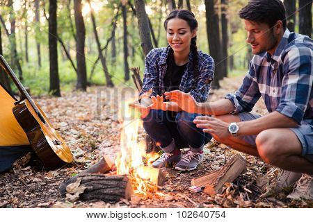 Happy couple and bonfire in the forest