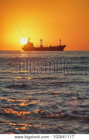 Cargo ship sailing near sea harbour on beautiful sunrise