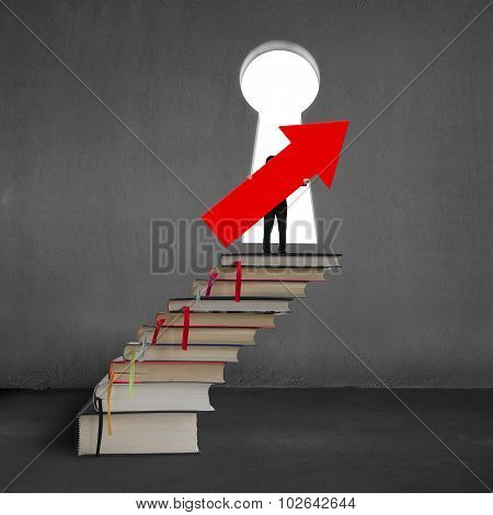 Man Holding Arrow Up Sign On Top Of Stack Books